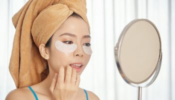 Asian woman with under-eye patches applying makeup