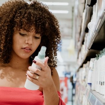 Happy young brunette with curly hair buying shampoo in supermarket